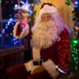 santa claus sitting beside lit tree